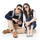 Happy traveling Asian couple sitting on ground Stock Images