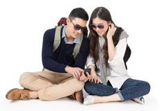 Happy traveling Asian couple. Sitting on ground and using cellphone, full length portrait on white background Royalty Free Stock Photo