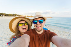 Happy traveling couple in love taking a selfie on phone at the beach on a sunny summer day. Pretty girl and her handsome Stock Photos