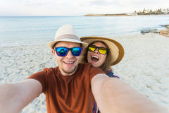Happy traveling couple making selfie sea background , sunny summer colors, romantic mood. Stylish sunglasses, straw hat Stock Images