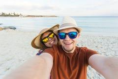 Happy traveling couple making selfie sea background , sunny summer colors, romantic mood. Stylish sunglasses, straw hat Stock Photos