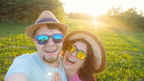 Happy traveling couple making selfie sunny summer colors at sunset