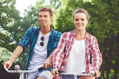 Happy traveling couple riding on bicycles. Boyfriend and girlfri Royalty Free Stock Images