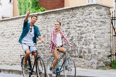 Happy traveling couple riding on bicycles. Boyfriend and girlfri Stock Images