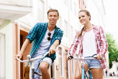 Happy traveling couple riding on bicycles. Boyfriend and girlfri Stock Image