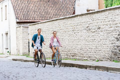 Happy traveling couple riding on bicycles. Boyfriend and girlfriend in old town. Love, relationship, romance concept. royalty free stock images