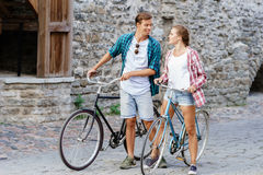 Happy traveling couple riding on bicycles. Boyfriend and girlfri Stock Photos