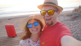 Happy traveling couple taking a selfie on phone at the beach. Happy traveling couple taking a selfie on phone at the sunset beach stock video