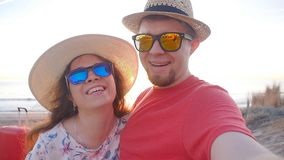 Happy traveling couple taking a selfie on phone at the beach. Happy traveling couple taking a selfie on phone at the sunset beach stock footage