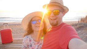 Happy traveling couple taking a selfie on phone at the beach. Happy traveling couple taking a selfie on phone at the sunset beach stock video footage