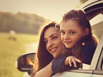 Happy traveling smiling mother and kid girl looking from the new. Car window on the beautiful nature background. Good purchase of vehicle royalty free stock image