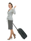 Happy traveling woman with suitcase waving hand Royalty Free Stock Photos