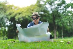 A happy traveller senior man sit in Forrest, opening a map royalty free stock image