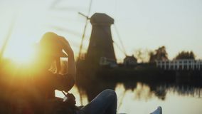 Happy traveller woman in hat watching sunset. Girl sitting on a beautiful lake pier with camera. Rustic wind mill. 4K. stock footage