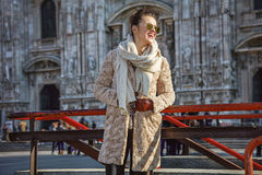 Happy traveller woman in Milan, Italy looking into distance. Rediscovering things everybody love in Milan. happy young traveller woman in fur coat and sunglasses Royalty Free Stock Image