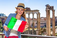 Happy traveller woman near Roman Forum showing Italian flag Stock Photo