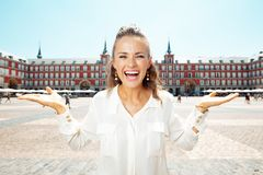 Happy traveller woman presenting something on empty palm. Happy elegant traveller woman at Plaza Mayor presenting something on empty palm royalty free stock photos