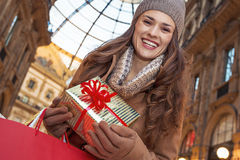 Happy traveller woman with shopping bags in Milan, Italy. On a huge Christmas sales in Italian fashion capital. Portrait of happy elegant traveller woman with Stock Image