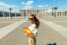 Happy traveller woman with Spain flag looking into distance. Happy stylish traveller woman with Spain flag looking into the distance near Royal Palace royalty free stock photo
