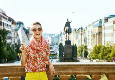Happy traveller woman on Vaclavske namesti in Prague with map Royalty Free Stock Photo