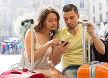 Happy travellers using mobile navigating system Royalty Free Stock Photography