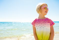 Happy trendy child in colorful shirt on beach looking aside Royalty Free Stock Photos