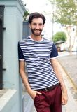 Happy trendy man in striped shirt leaning against wall outdoors Royalty Free Stock Images