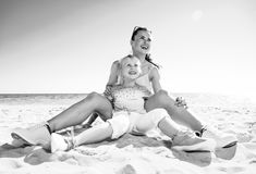 Happy trendy mother and child on beach looking into distance. Colorful and wonderfully cheerful mood. happy trendy mother and child in colorful clothes on the Stock Image