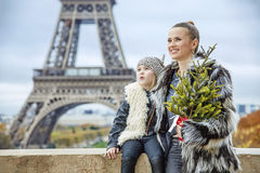 Happy trendy mother and child with Christmas tree in Paris. The Party Season in Paris. happy trendy mother and child with Christmas tree against Eiffel tower in Royalty Free Stock Image