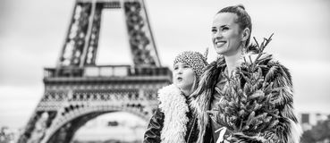 Happy trendy mother and child with Christmas tree in Paris. The Party Season in Paris. happy trendy mother and child with Christmas tree against Eiffel tower in Stock Photos