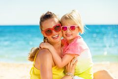 Happy trendy mother and child in colorful clothes on beach. Colorful and wonderfully cheerful mood. Portrait of happy trendy mother and child in colorful clothes Royalty Free Stock Photo