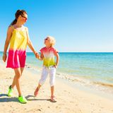 Happy trendy mother and child on seacoast walking. Colorful and wonderfully cheerful mood. Full length portrait of happy trendy mother and child in colorful Royalty Free Stock Image
