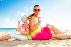 Happy trendy mother and child on seashore blowing bubbles. Colorful and wonderfully cheerful mood. happy trendy mother and child in colorful clothes on the Royalty Free Stock Photos