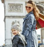 Happy trendy mother and child shopper in Paris, France. Stylish autumn in Paris. happy trendy mother and child with shopping bags in Paris, France Stock Photos