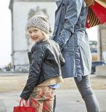 Happy trendy mother and child shopper in Paris, France. Stylish autumn in Paris. happy trendy mother and child with shopping bags in Paris, France Royalty Free Stock Photos