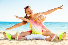 Happy trendy mother and daughter on seacoast having fun time. Colorful and wonderfully cheerful mood. happy trendy mother and daughter in colorful clothes on the stock photo