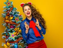 Happy trendy woman near Christmas tree with crossed fingers. Festive season. happy trendy woman near Christmas tree isolated on yellow background with crossed Royalty Free Stock Photos