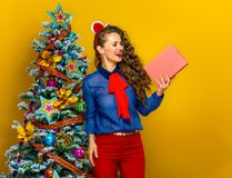 Happy trendy woman near Christmas tree looking at book Royalty Free Stock Photography