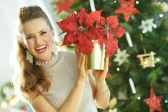 Happy woman near Christmas tree showing red poinsettia. Happy trendy woman near Christmas tree showing red poinsettia stock photography