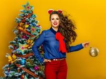 Happy trendy woman woman holding Christmas ball Royalty Free Stock Photos