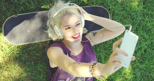 Happy trendy young blond female student. Listening to music on headphones taking her selfie on her mobile as she lies on the grass with her head on a skateboard stock video