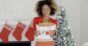 Happy trendy young woman with a Christmas dessert. Or pastry balanced on her hands standing in front of the decorated tree and chimney smiling at the camera stock video
