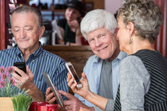 Happy  Trio in Coffee House Using Electronic Devices Stock Images