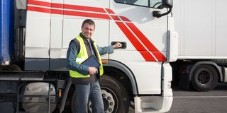 Happy trucks driver in front of container delivery truck royalty free stock photo