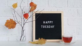 Happy Tuesday text on black letter board and bouquet of branches with yellow leaves on clothespins in vase on table. Template for postcard, greeting card stock video