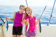 Happy tuna fisherwomen kid girls with fishes catch. Happy tuna fisherwomen kid girls on boat with fishes trolling catch Royalty Free Stock Photos