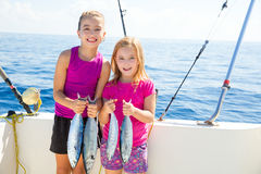 Happy tuna fisherwomen kid girls with fishes catch Stock Images
