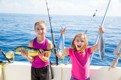 Happy tuna fisherwomen kid girls with fishes catch. Happy tuna fisherwomen kid girls on boat with fishes trolling catch with dorado Mahi Royalty Free Stock Photos