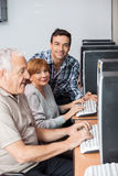Happy Tutor With Senior Students In Computer Class Royalty Free Stock Images