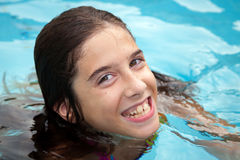 Happy Tween Girl In Swimming Pool. A happy tween girl in a swimming pool smiles with crooked teeth.  Her lips and gums are slightly blue because she is cold Royalty Free Stock Images